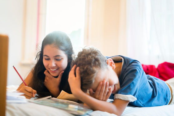 A photo of happy siblings enjoying while lying on bed. Teenager writing while boy covering face. They are at home.