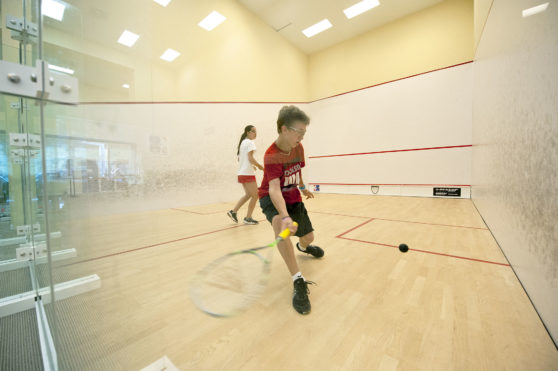 Cameron Burton goes for a forehand against Cameron Munn during the squash summer camp at the Elmaleh-Stanton Squash Center at the SYS facility in Southampton on Monday, 7/2/12